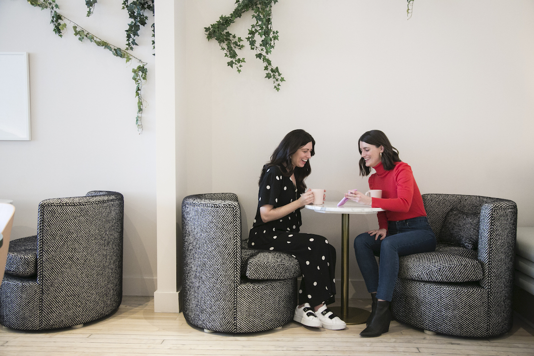 Two smiling women sit in large, cozy armchairs sharing coffee and looking at Instagram Stories together on and iPhone.