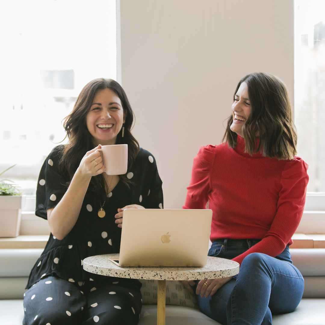 Two smiling women with wavy brown hair share coffee and look at a laptop together. They are seated at a comfy booth in front of a pink marble table.
