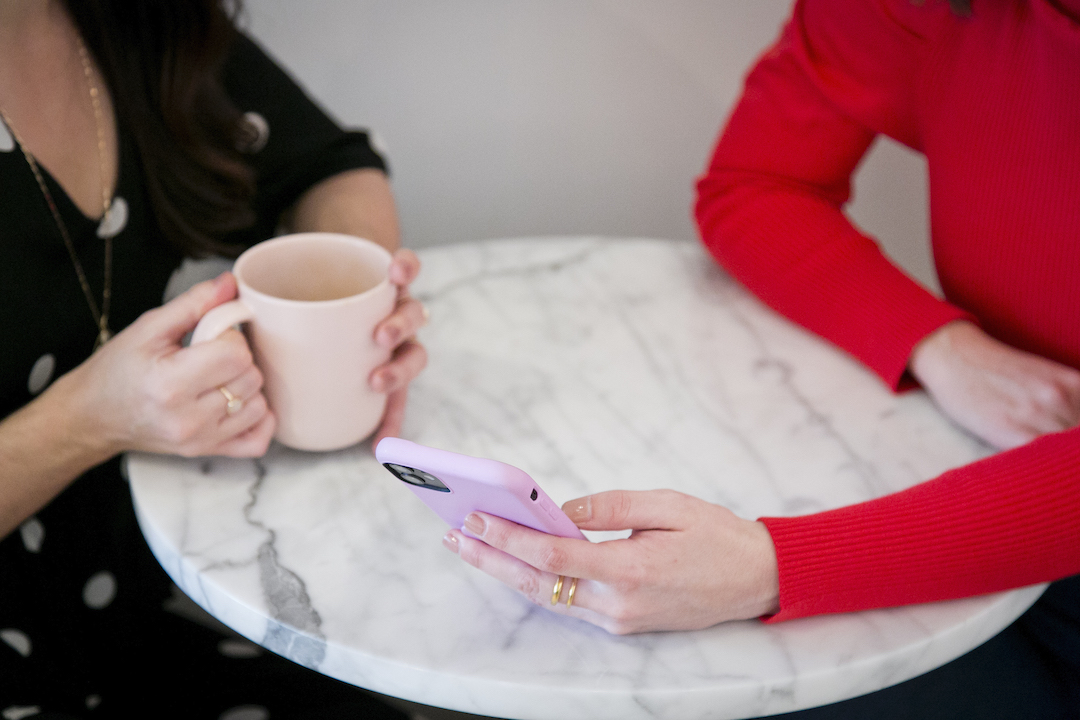 Two women, whose faces are out of frame, sit together at a white marble table sharing coffee and looking at a pink mobile telephone.
